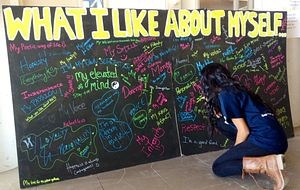 Picture of a Centennial College student writing on the What I Like About Myself art board
