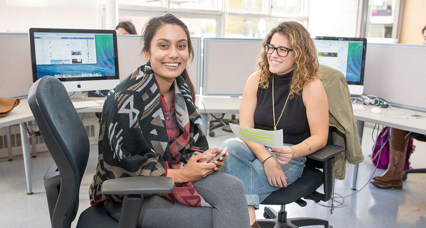 picture of two Centennial College Advertising and Marketing Communications Management program students in a computer lab smiling