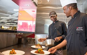 picture of two Centennial College cafeteria chefs in the kitchen preparing food