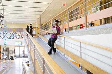 picture of a Centennial College student standing in the Story Arts Centre campus hallway holding a laptop