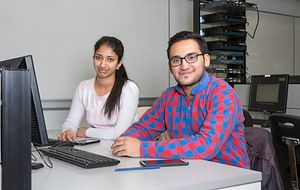 picture of two centennial college students in a computer lab completing the student satisfaction and engagement survey