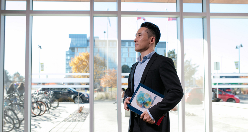picture of a centennial college global business management student dressed in business professional standing in a building entry way