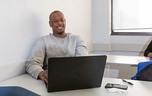 picture of a centennial college student on a laptop in class