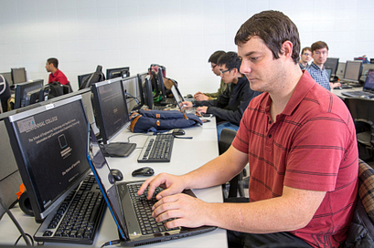 Male student in a computer lab working on his computer