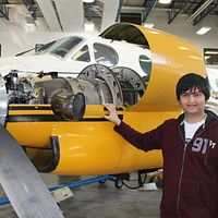 Picture of Asad Muhammad from the Lego project next to a plane