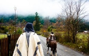 Picture of a Centennial College student riding on a horse wearing a poncho and riding towards a mountain in Peru