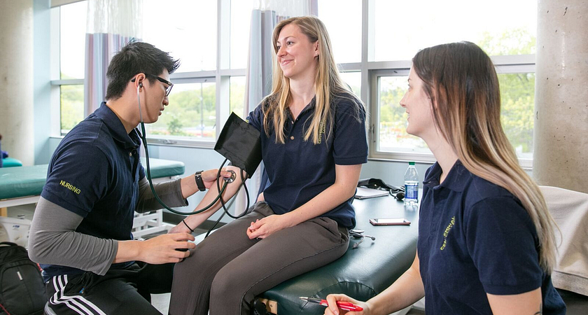 Picture of three nursing students in the classroom checking a woman's pulse with a stethoscope
