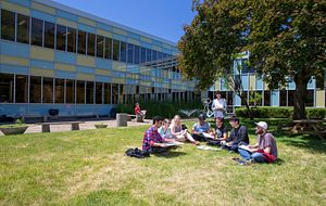 picture of Centennial College students sitting in a circle on the grass outside the Story Arts Centre