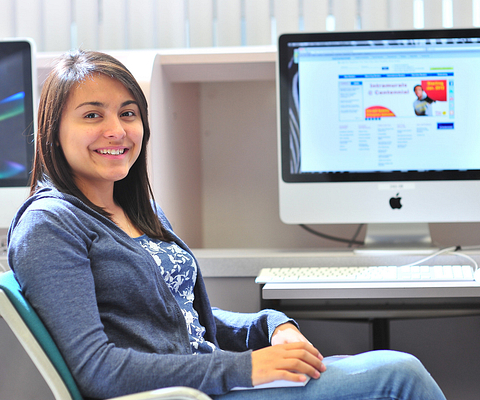 Female Aboriginal student lays back on a chair, with a Mac computer on the background with the MyCentennial website in the background