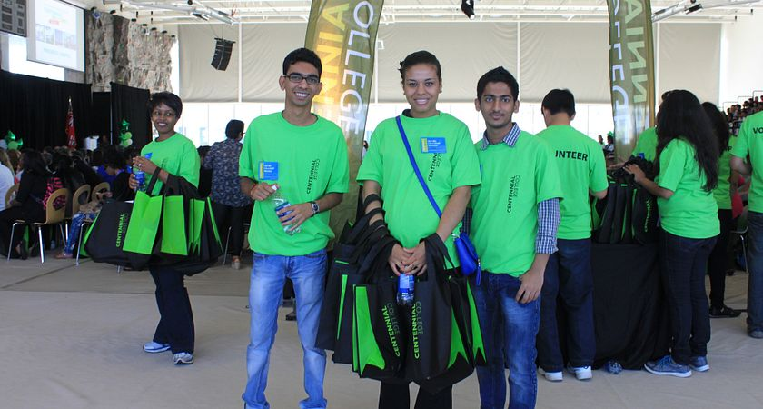 Three Centennial College ambassadors, wearing their green Centennial t-shirts, poses during Centennial Welcomes 2012, with one of them holding swag bag for guests