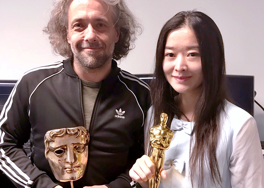Picture of Centennial College graduate and Visual Effects Oscar winner Jiayin Wang with colleague holding a BAFTA award