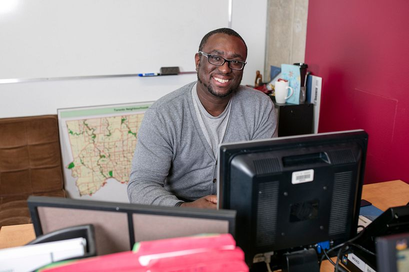 centennial college alumni member smiling while reading the newsletter on his computer