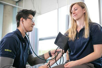 Nursing student wearing dark blue scrubs checking another student's blood pressure