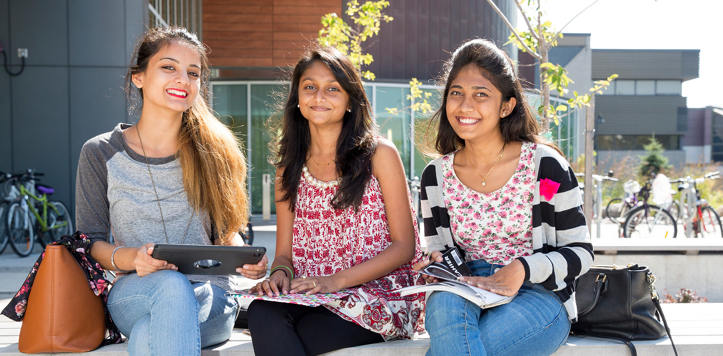 picture of Centennial College International Education students sitting outside Progress Campus library smiling