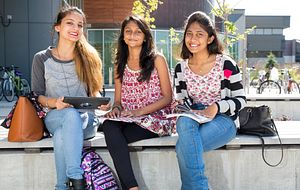 Picture of Centennial College students sitting outside the Progress Campus library smiling