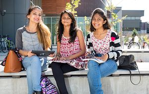picture of three centennial college students sitting outside progress campus on a bench