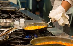 picture of Centennial College chef cooking with a pan on a stove