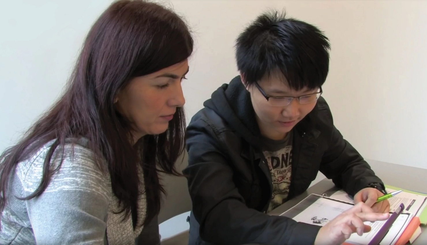 two people sitting at a desk looking at study notes