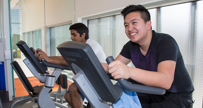 picture of centennial college students biking on exercise bikes smiling