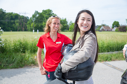 picture of a centennial college motorcycle rider training student smiling holding a helmet with their instructor