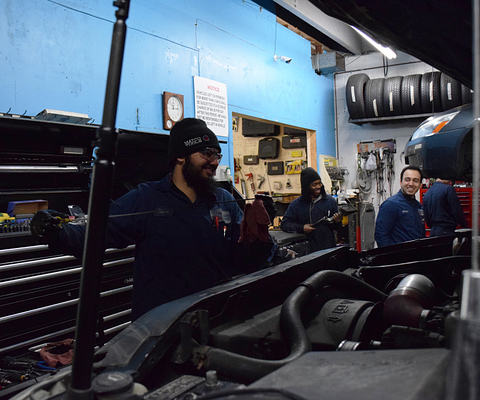 Picture of Automotive Technician Apprenticeship Students Umer Bhagoo and Nicholas Lewis working with their supervisor on the job