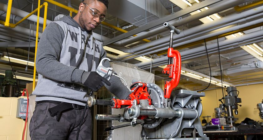 A picture of a student in Heating, Refrigeration and Air Conditioning repairing a unit.