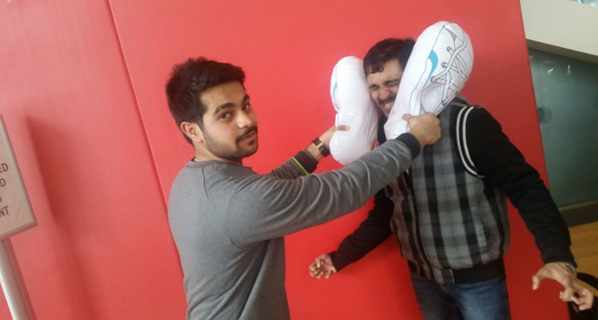A pair of Centennial College students posing with Shoesie, Centennial Chase's mascot