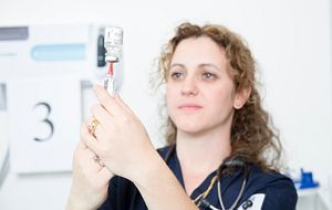 picture of a nurse preparing a needle for a flu shot